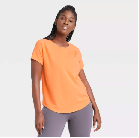 a model wearing the orange crewneck shirt