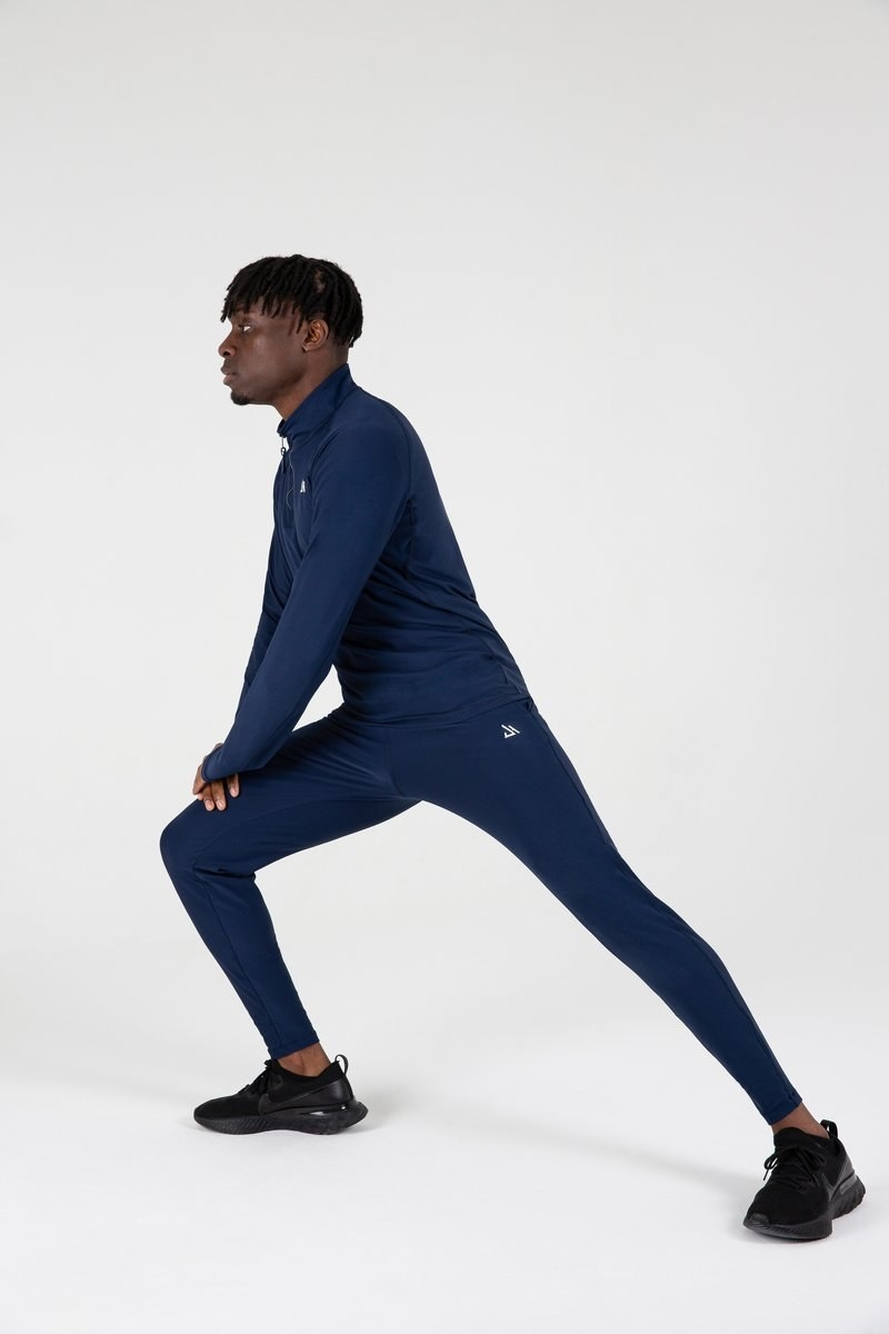 a model wearing the tapered navy joggers and stretching
