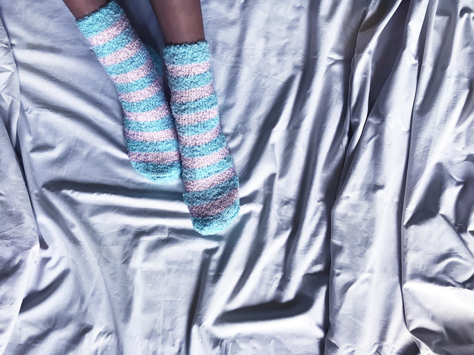 A person wearing striped socks in bed