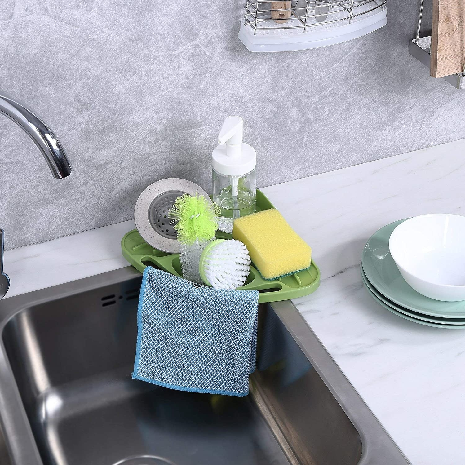 the caddy suctioned to on corner of the sink and holding a rag, two brushes, a sponge, a drainer, and dish soap
