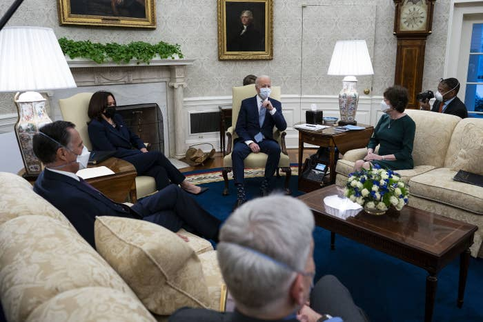 Lawmakers sit socially distant on couches around the Oval Office in masks