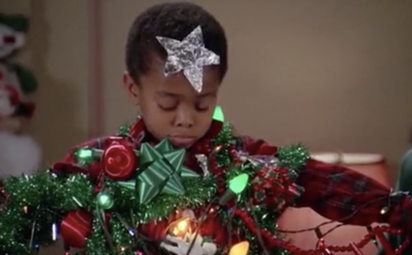 A little boy wrapped like a christmas present, looking sad.