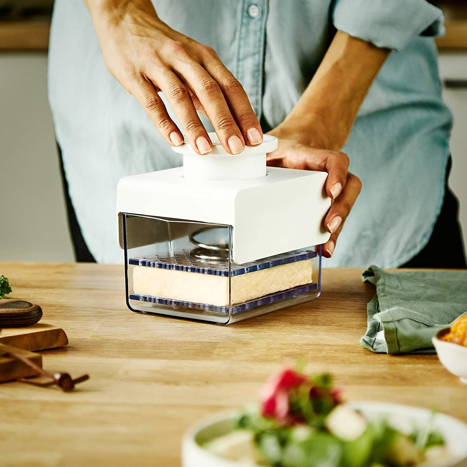 A person pressing tofu with the device