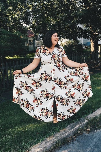 A reviewer wearing the short-sleeve, button-front maxi in white with red and yellow flowers