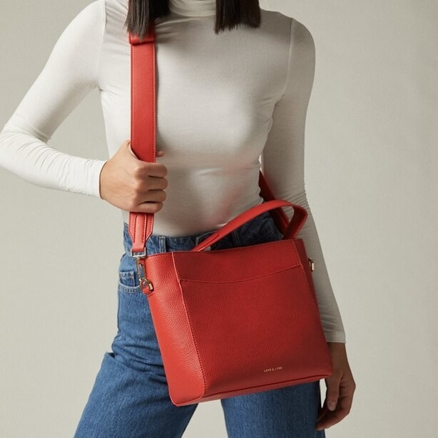 A person wearing a large purse with a wide strap across their chest