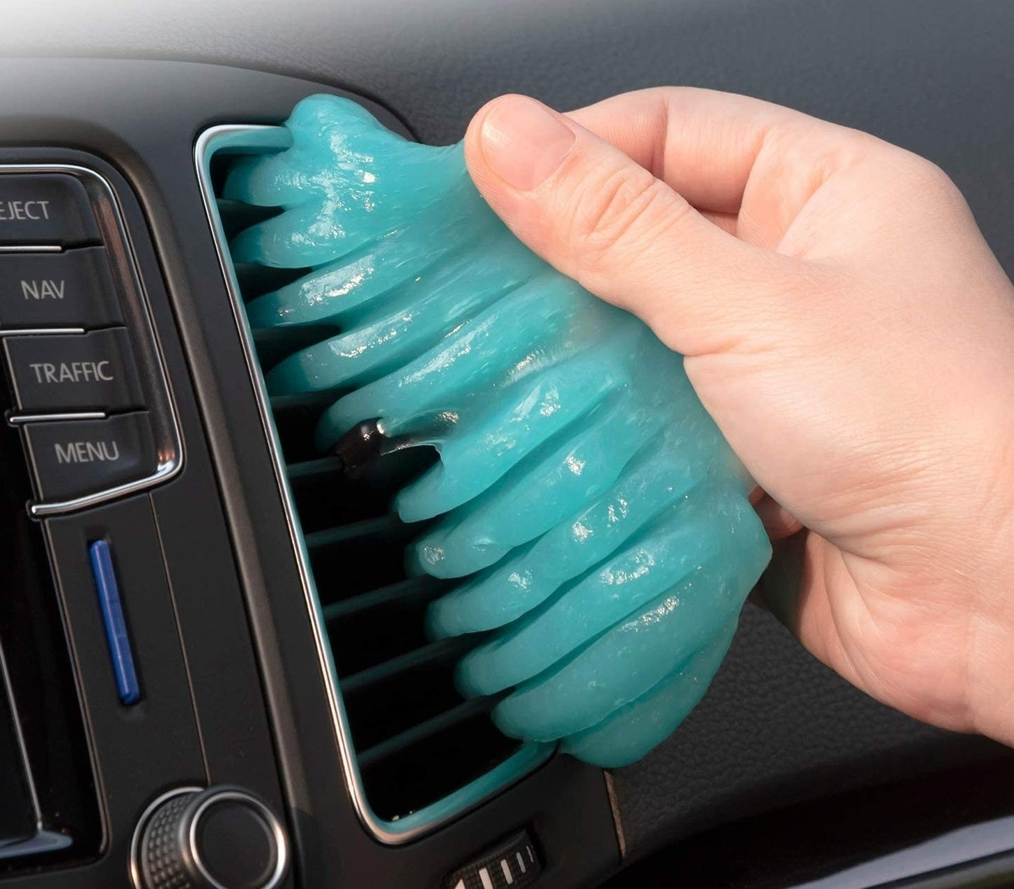 a hand pulls the cleaning putty out of a car vent