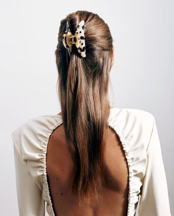 A woman with long straight hair wearing the blonde tortoise shell clip