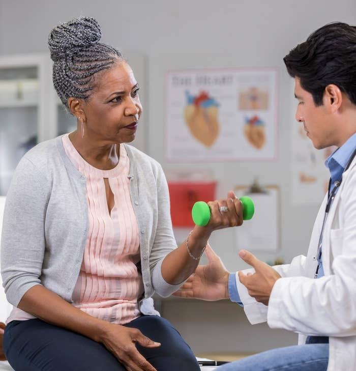 A white male doctor stands beside his senior Black female patient