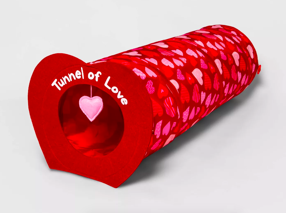 Bright red heart-covered tunnel toy with felt front, silky inside, and hanging toy in front of hole opening