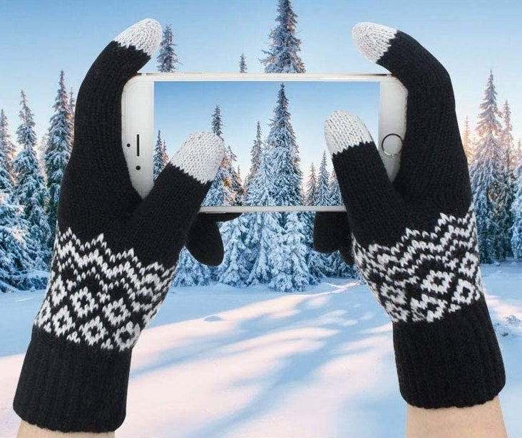 A person taking a picture while wearing the gloves