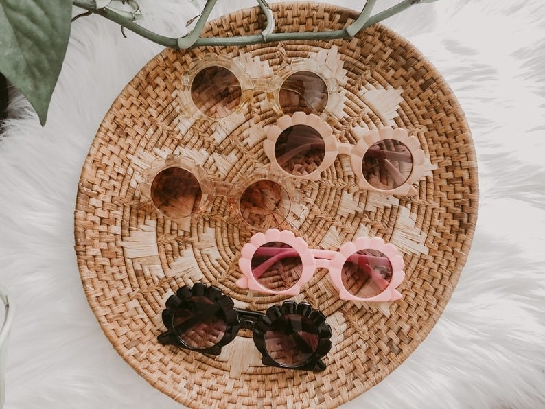 woven basket with five pairs of differntly colors sunglasses with the frame that look like seashells