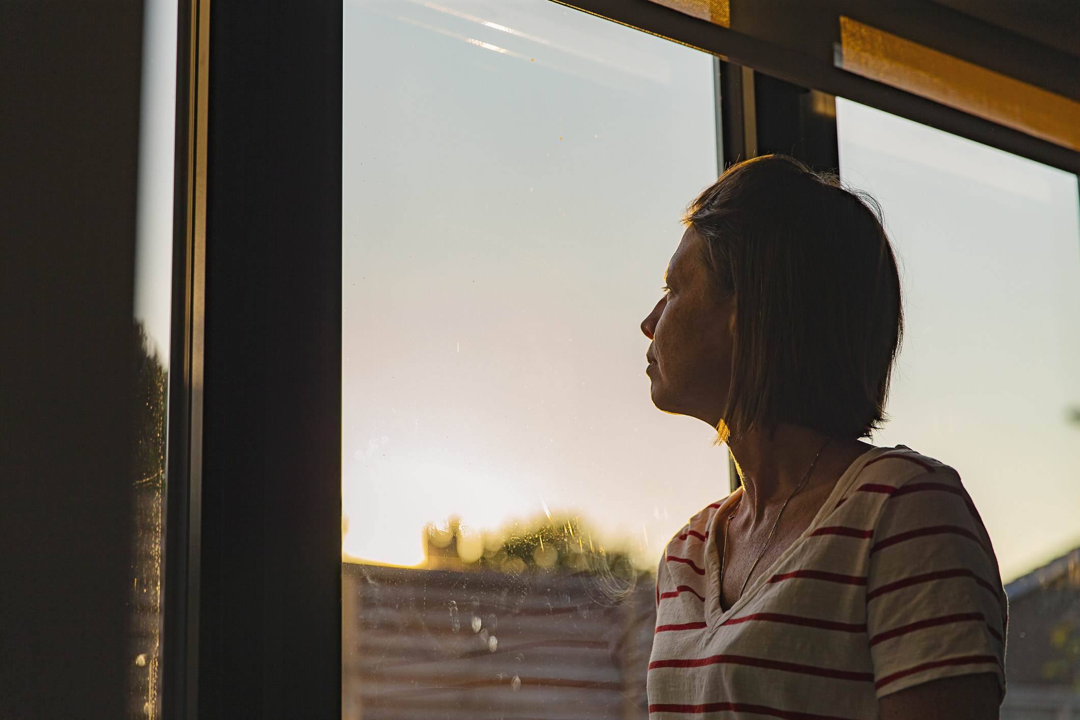 A woman looking out a window pensively