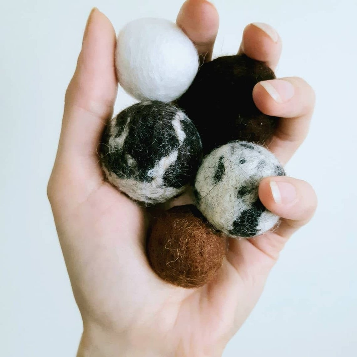 Person holding five felted wool balls in their hand