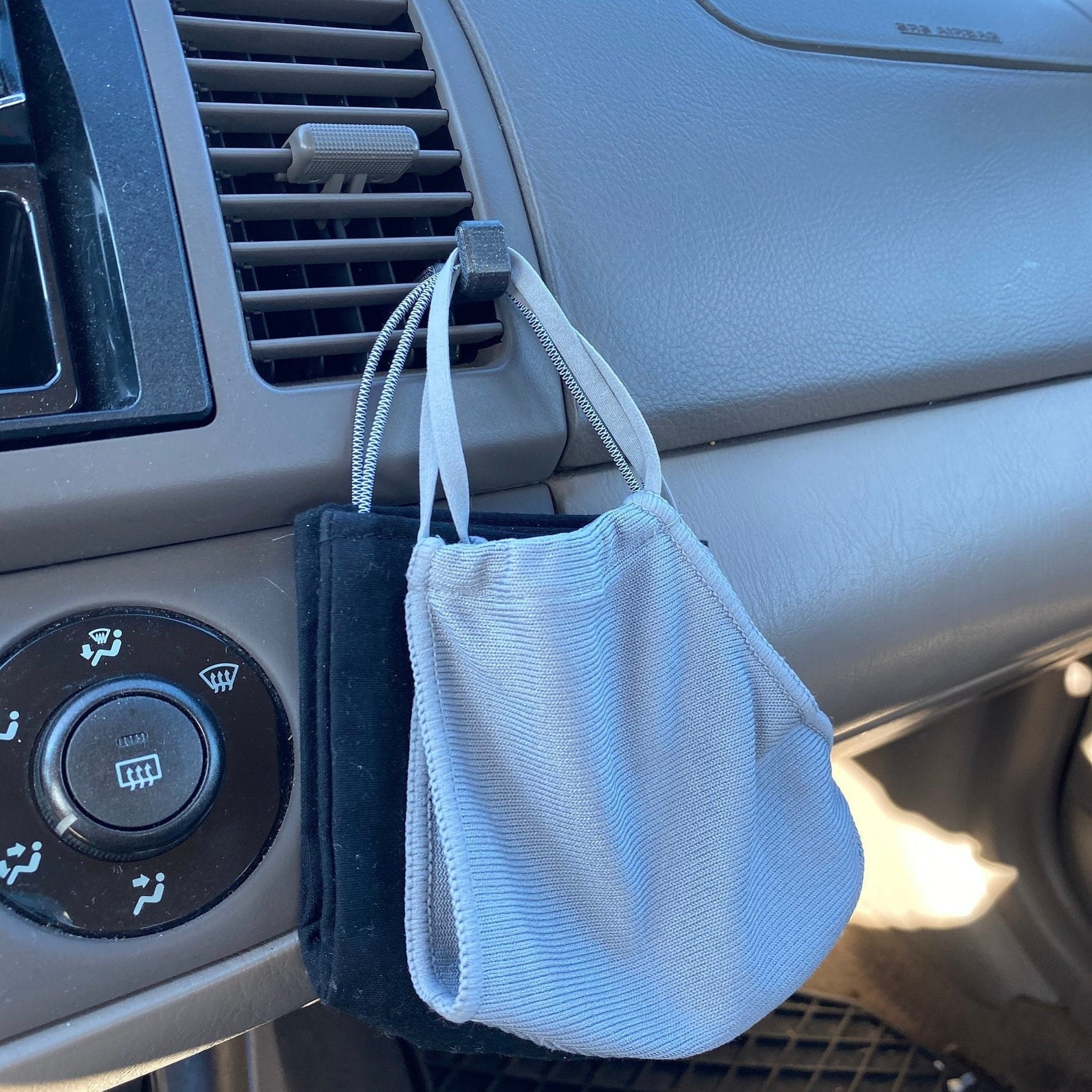 A small gray clip on an air conditioning vent in a car with masks hanging from it
