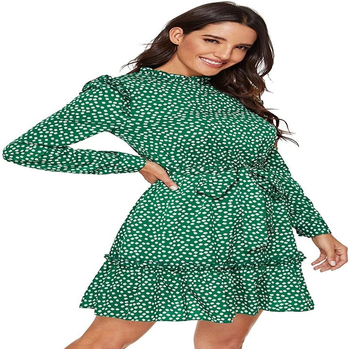 Model wearing the tie-waist long-sleeve dress in green printed with little white daisies