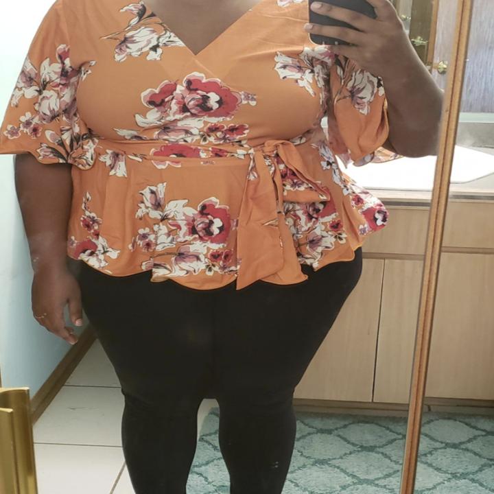 reviewer wearing top in mirror selfie in orange