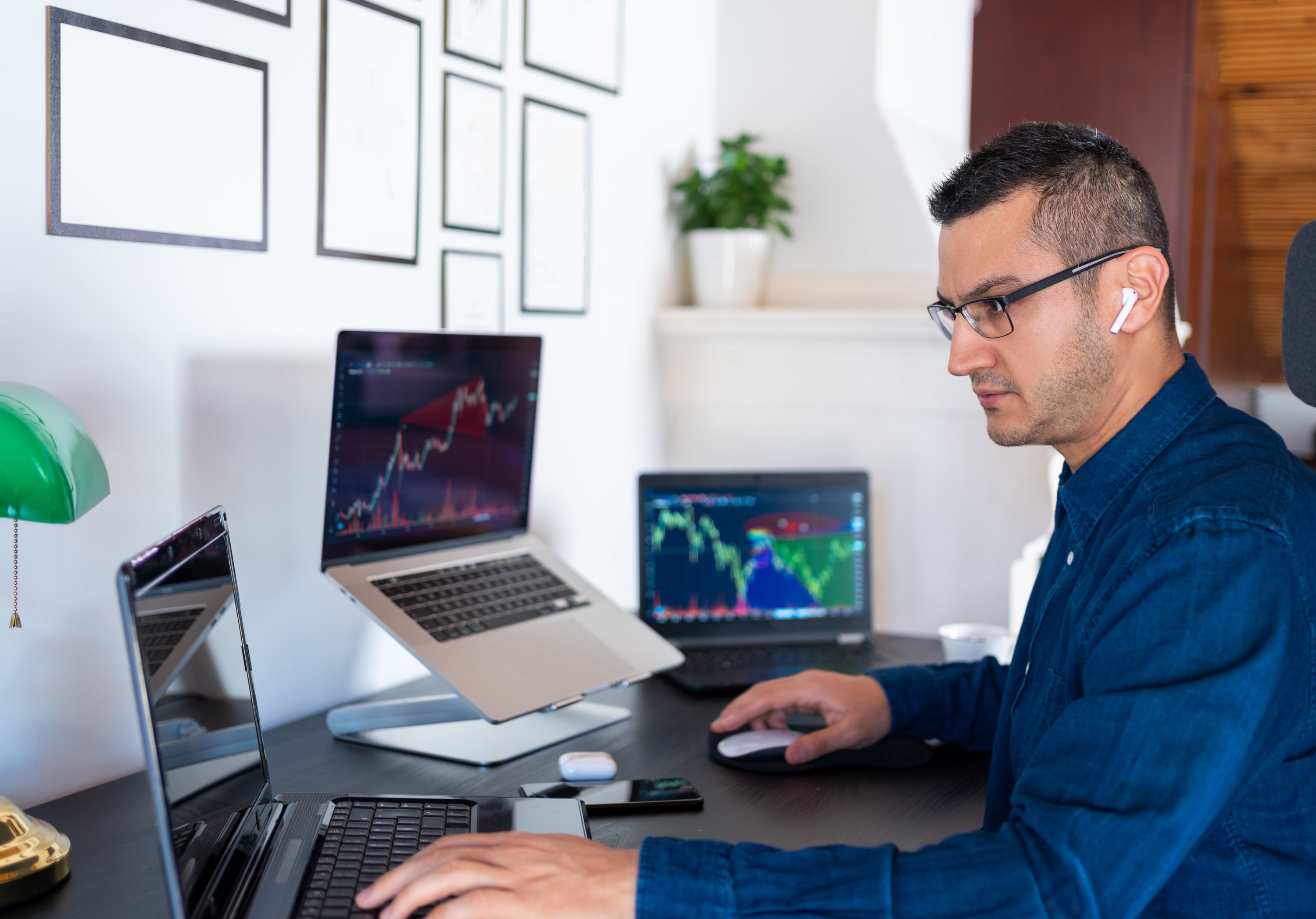 Man looking at his investments on three different laptops in his home office