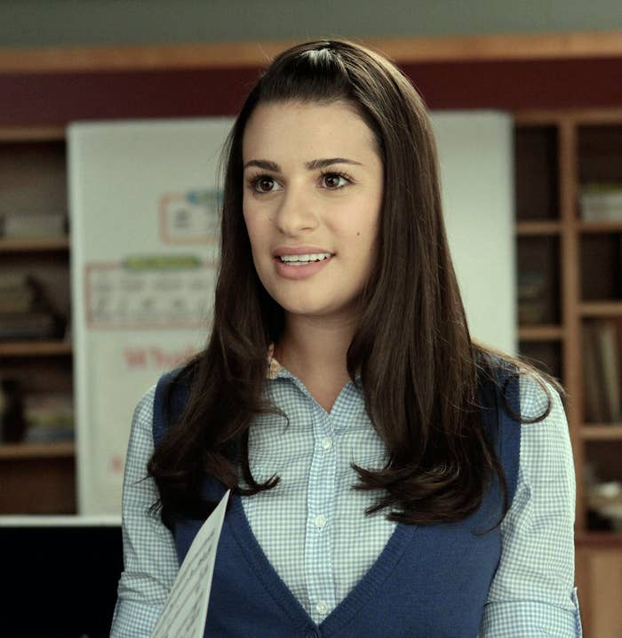 Rachel talking in a button-down and vest