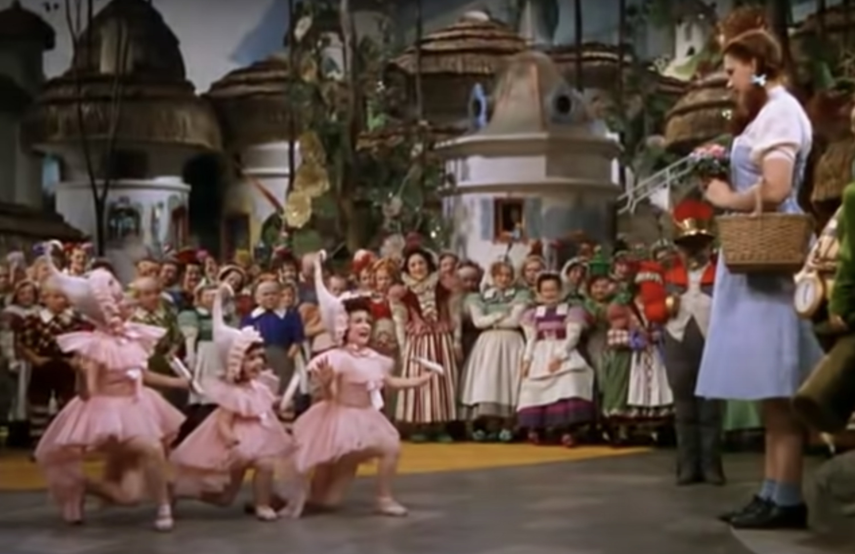 Judy Garland standing in Munchkinland with the ballerinas