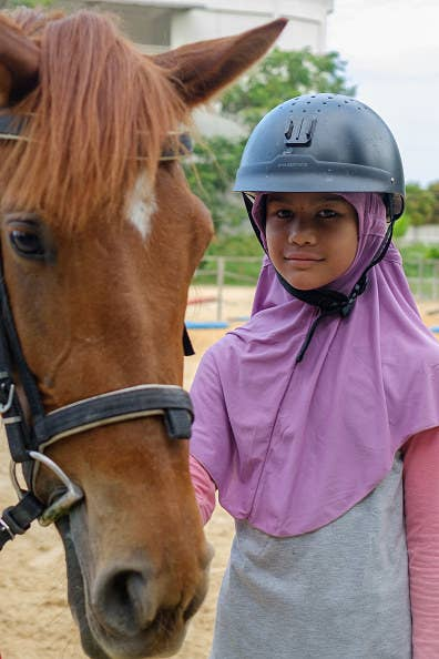Girl standing with horse