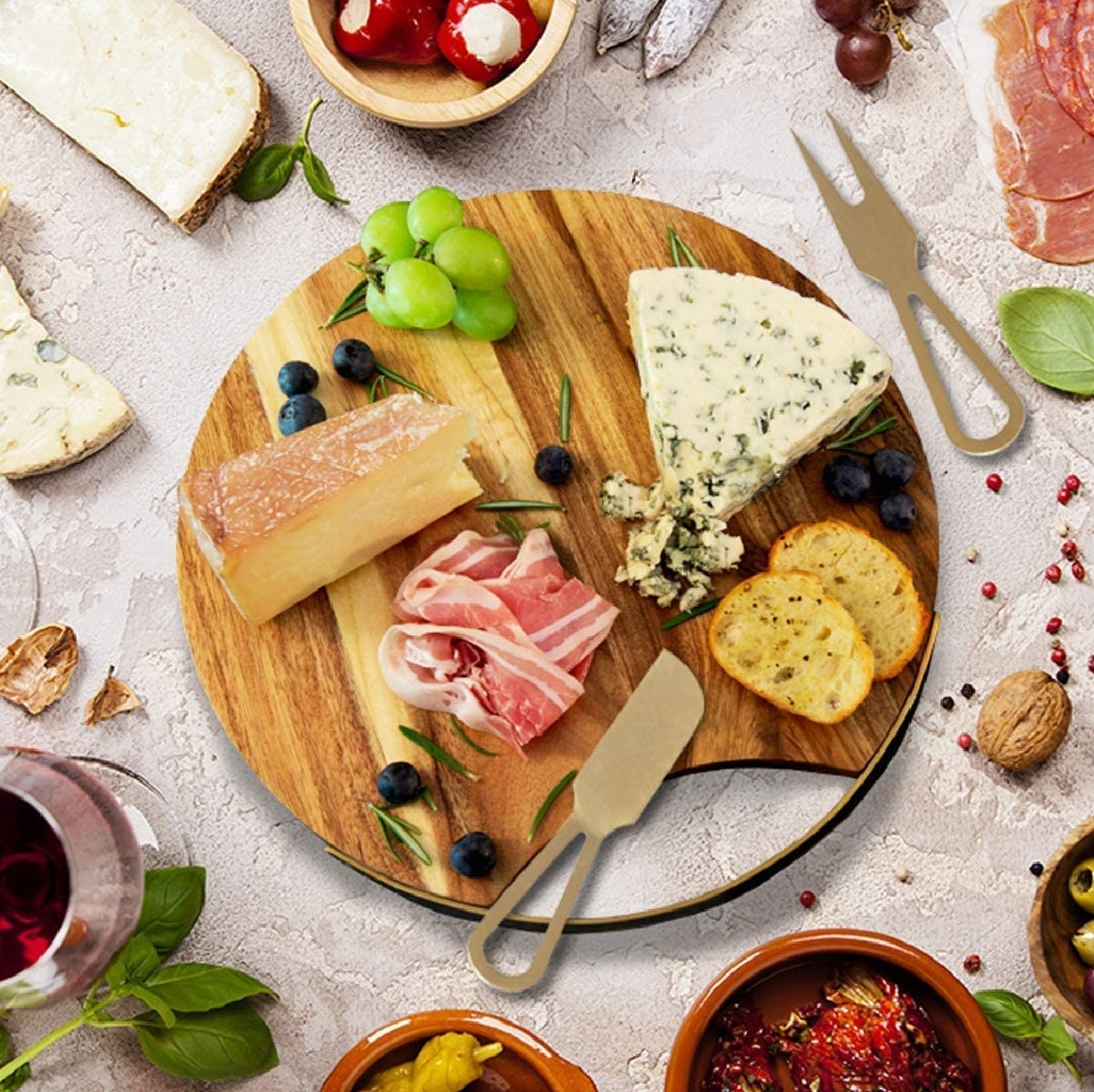 Wood circular cheese board with gold detailing on the side loaded with meats and cheese