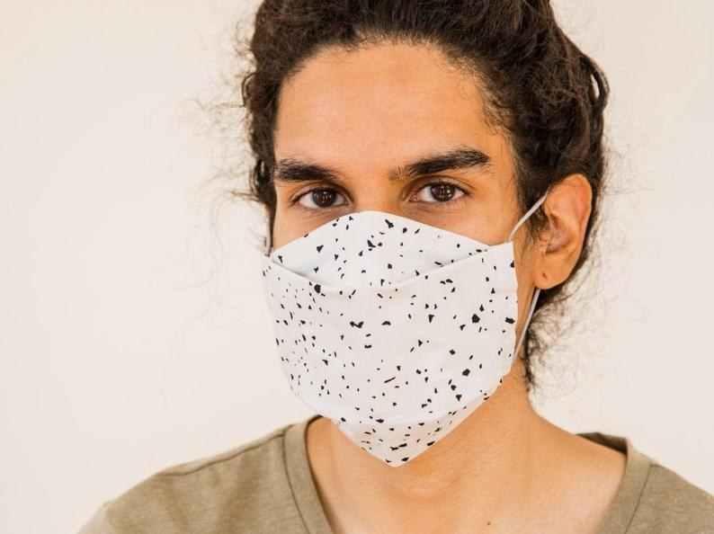 Model in white face mask with black speckled