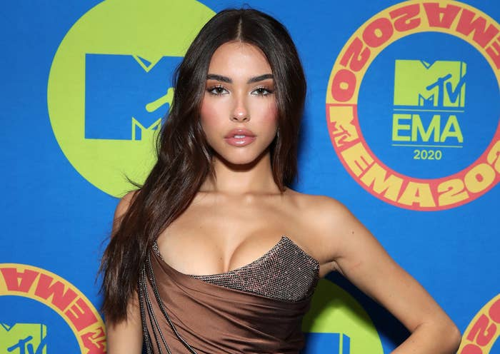 Madison wears a strapless brown dress while posing on a red carpet