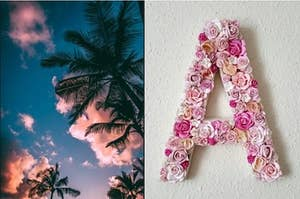 """A ground view of a sunset sky with clouds surrounded by palm trees and the letter """"A"""" made of flowers."""