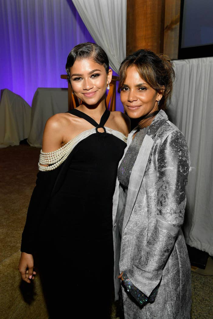Zendaya's wearing an off-the-shoulder dress with strings of pearls as she poses with Halley Berry who's wearing a dress and matching coat