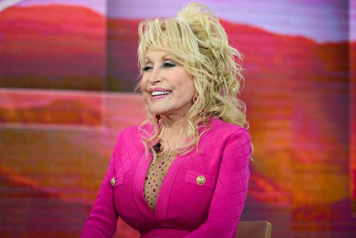 Dolly Parton wears a dress with buttons as she smiles at NBC Studios