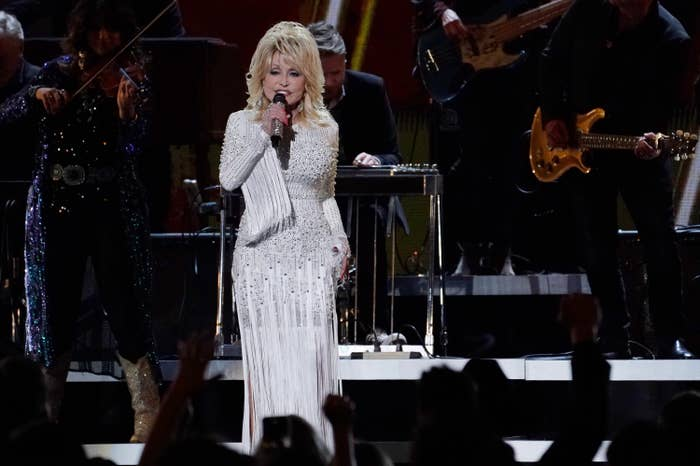 Dolly Parton, wearing a white dress, performs at the 2019 CMA Awards in Nashville