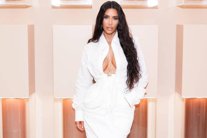 Kim Kardashian posing in a long-sleeved, open-necked shirtdress
