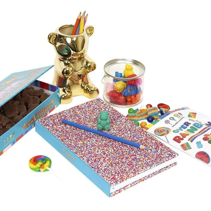 the kit with bag of colorful candy, gold gummy bear pencil cup, sprinkle notebook, gummy bear erasers, and box of animal crackers