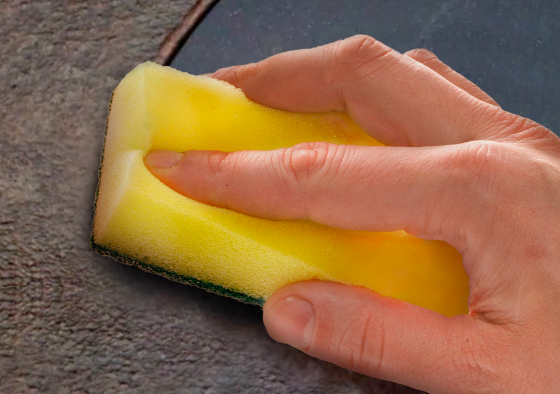 Hand with sponge wiping off grime from oven