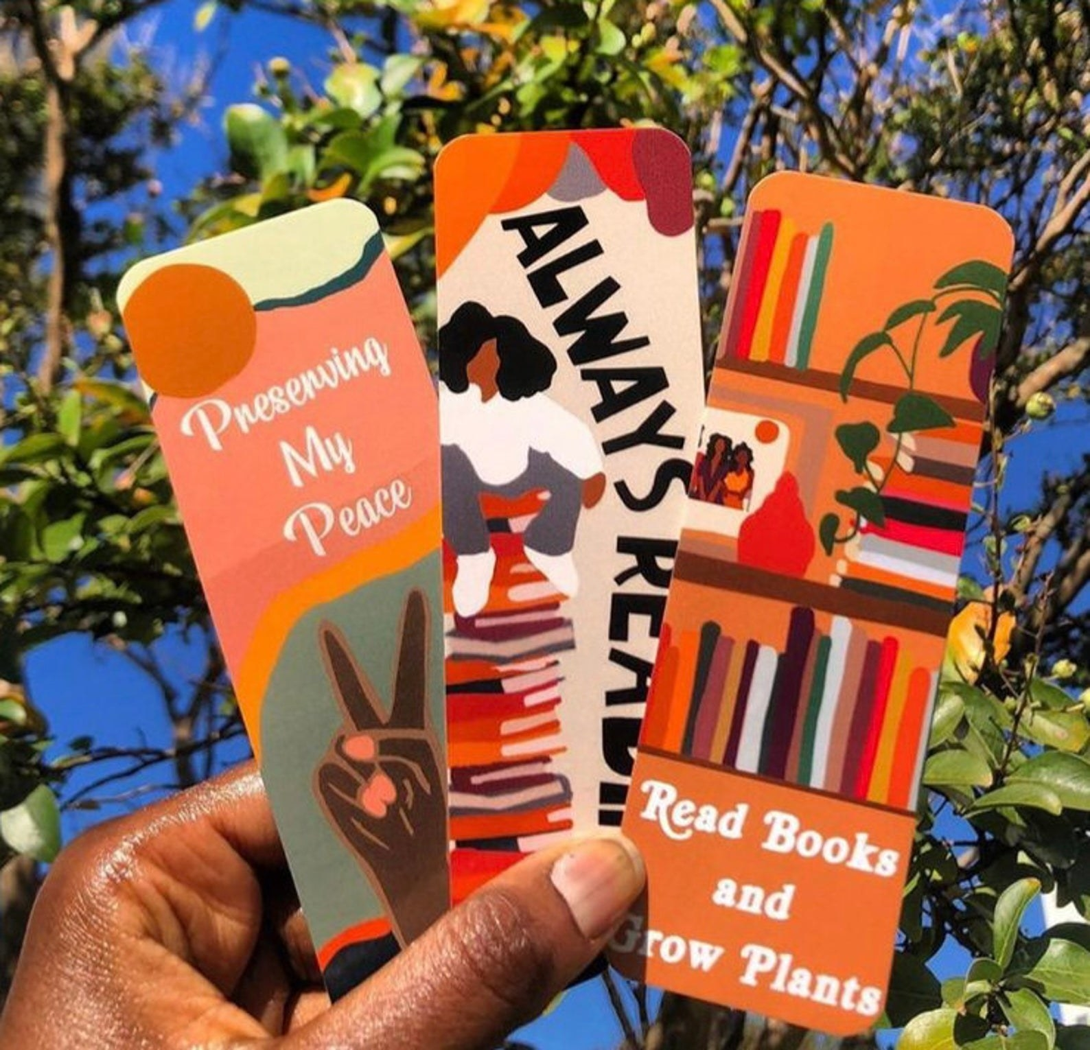 """Model's hand holding three bookmarks with bright illustrations of books and a peace sign. They say, """"Preserving my peace,"""" """"Always reading,"""" and """"Read books and grow plants,"""" respectively."""