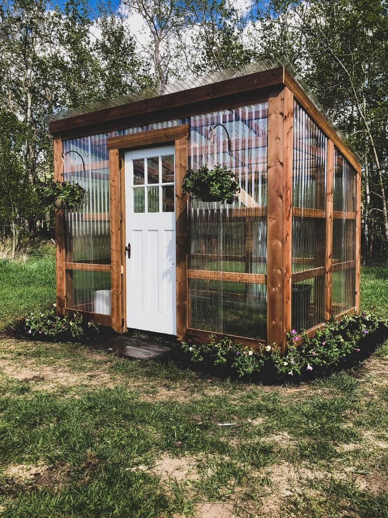 a greenhouse made of wooden planks, a wooden door, and clear siding