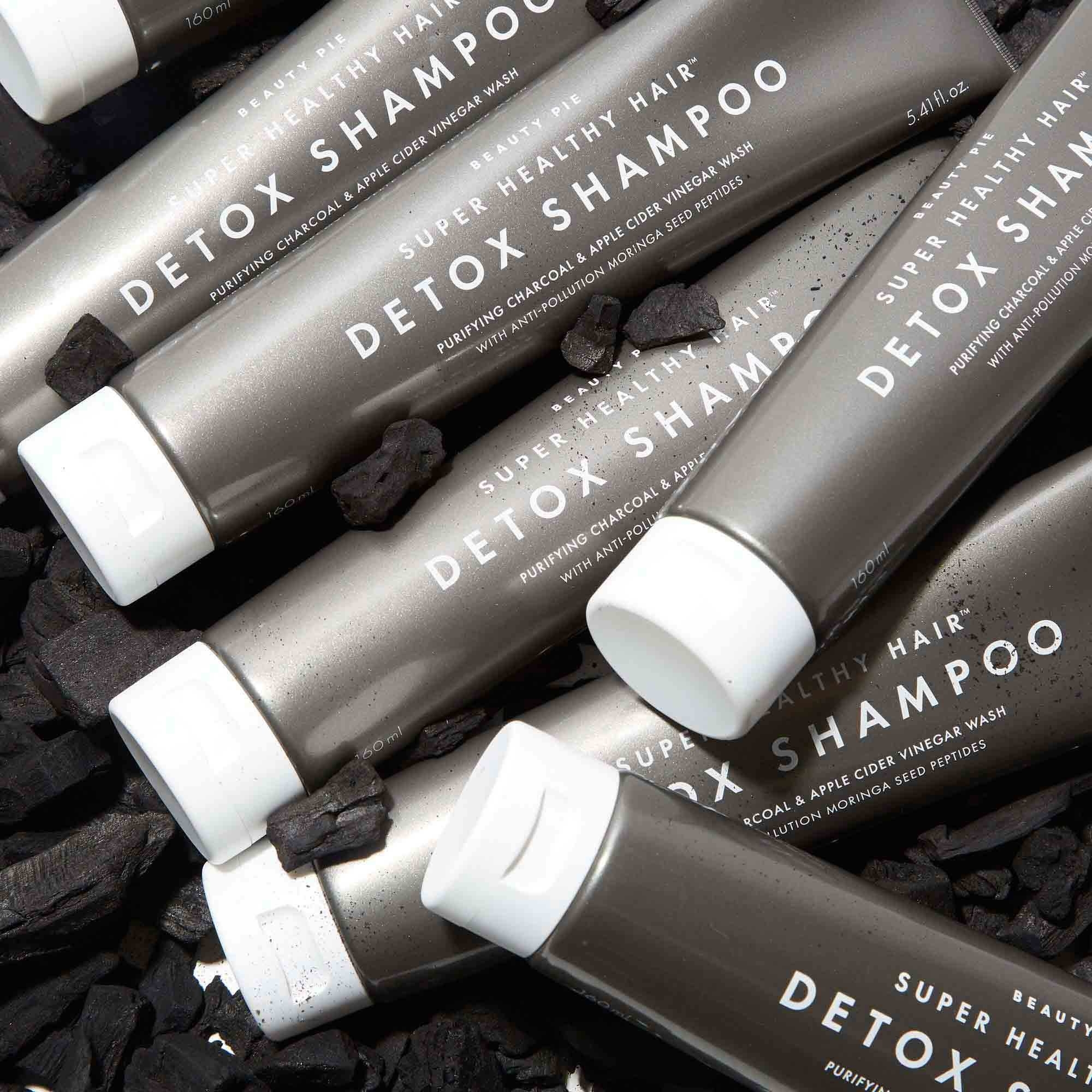 bottles of their detox shampoo styled on bed of charcoal