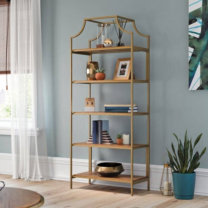 gold open-shelved bookcase in a well-lit room