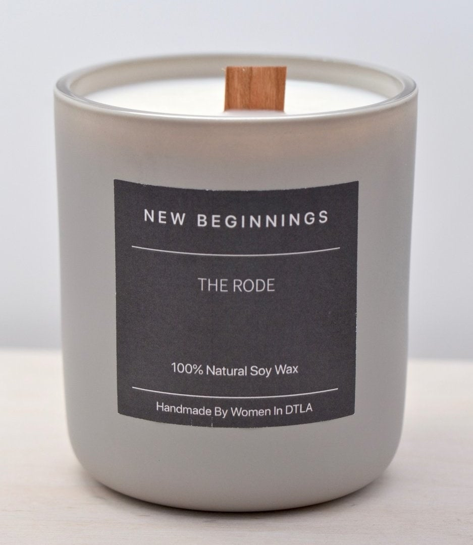 "a candle with a wood wick and a label that says ""new beginnings"""