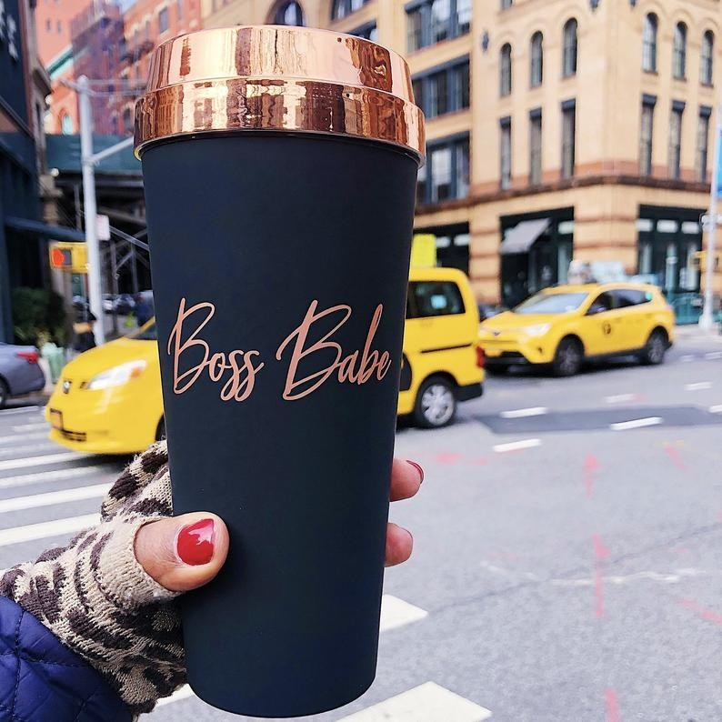 a hand holding the boss babe rose gold matte black travel mug on a busy city street