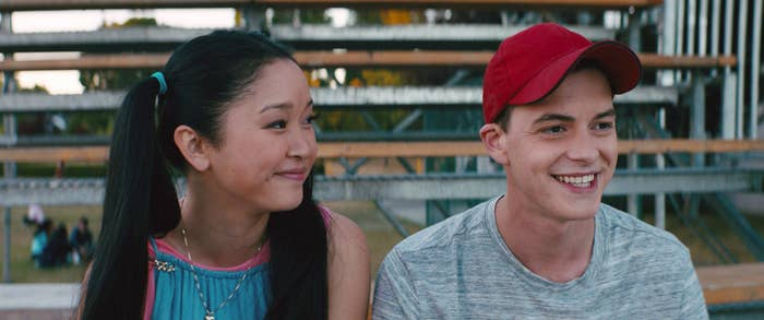 Lana Condor, in pigtails, and Israel Broussard, wearing a baseball cap, seating on bleacher seats in To All theBoys I've Loved Before