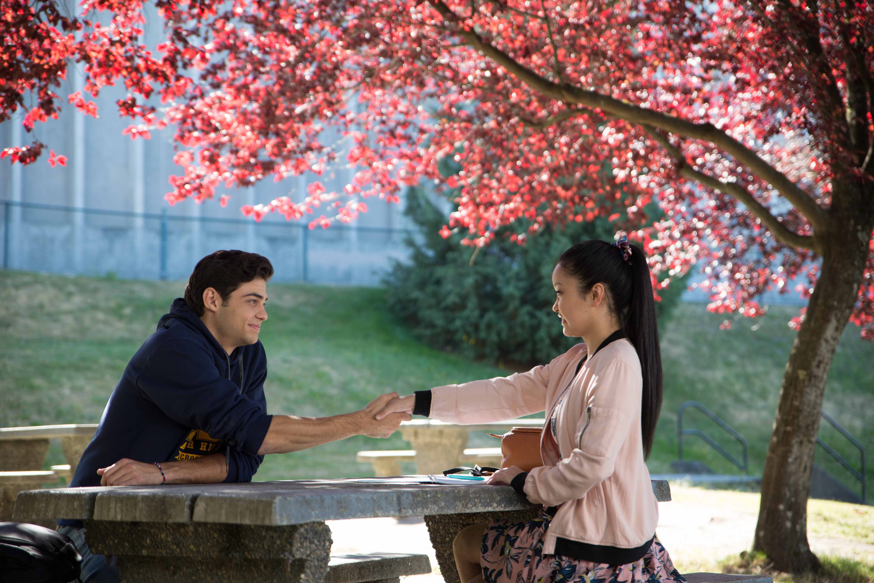 Noah Centineo and Lana Condor sit at a picnic table in To All the Boys I've Loved Before