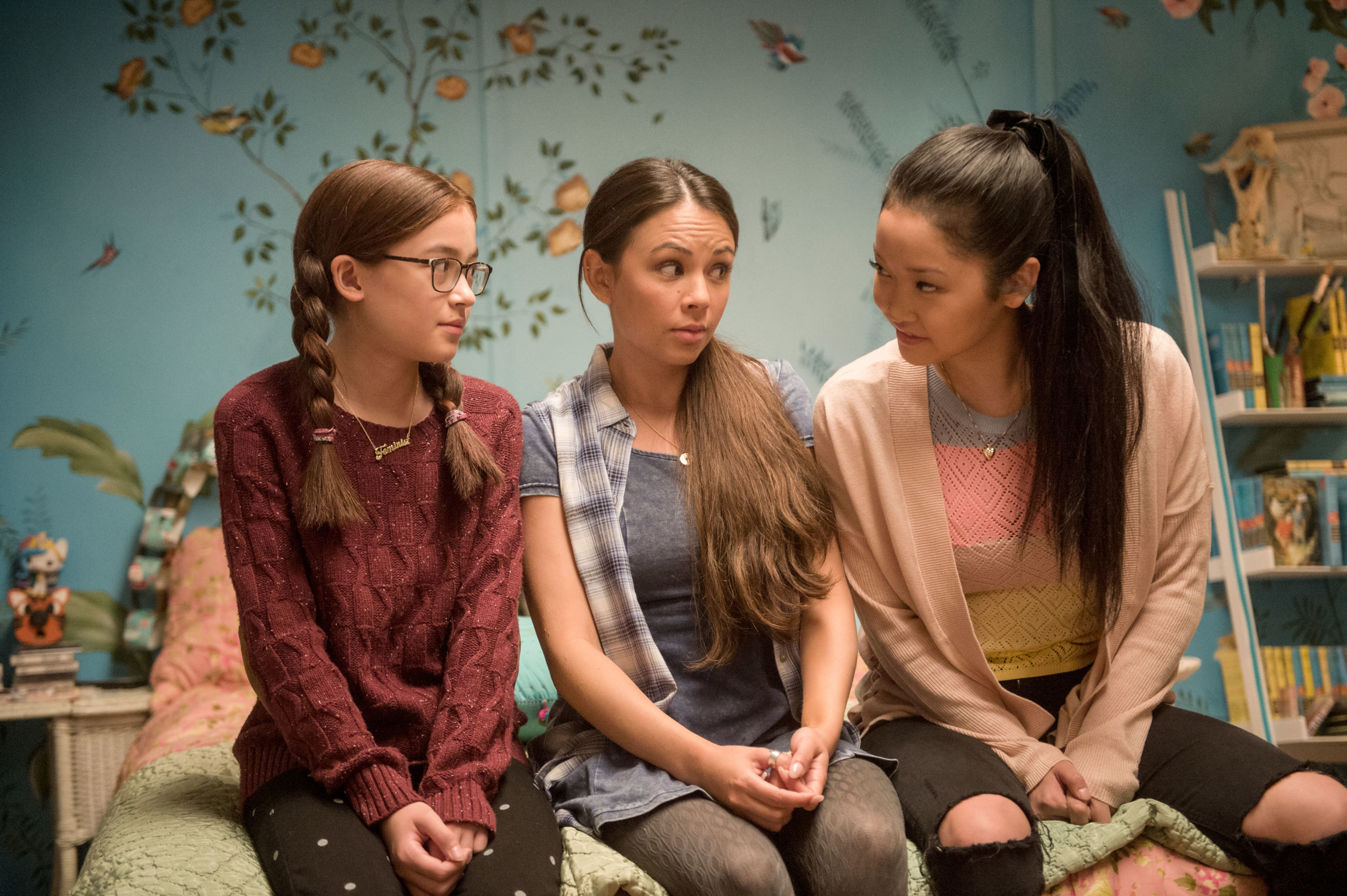 Anna Cathcart, Janel Parrish, and Lana Condor sit on a bed in To All the Boys I've Loved Before
