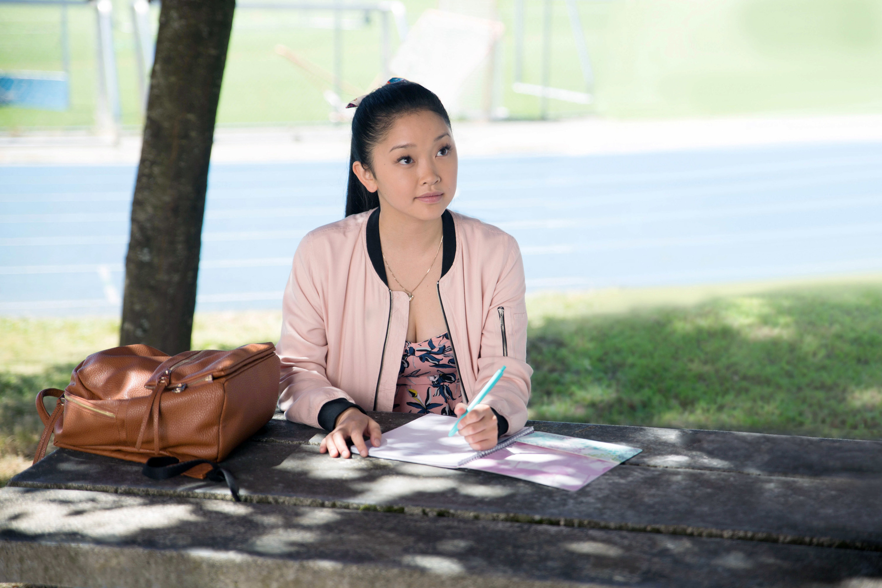 Lana Condor sits at a park bench with a bag by her side, holding a pen above a spiral notebook, in To All the Boys I've Loved Before