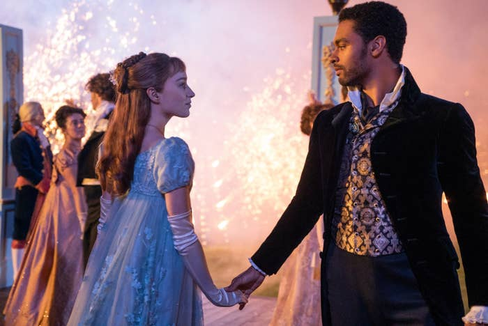 Phoebe Dynevor, wearing a gown and long gloves, and Rege-Jean Page, wearing a jacket, pants, and a patterned vest, hold hands as they look into each other's eyes at a party in Bridgerton