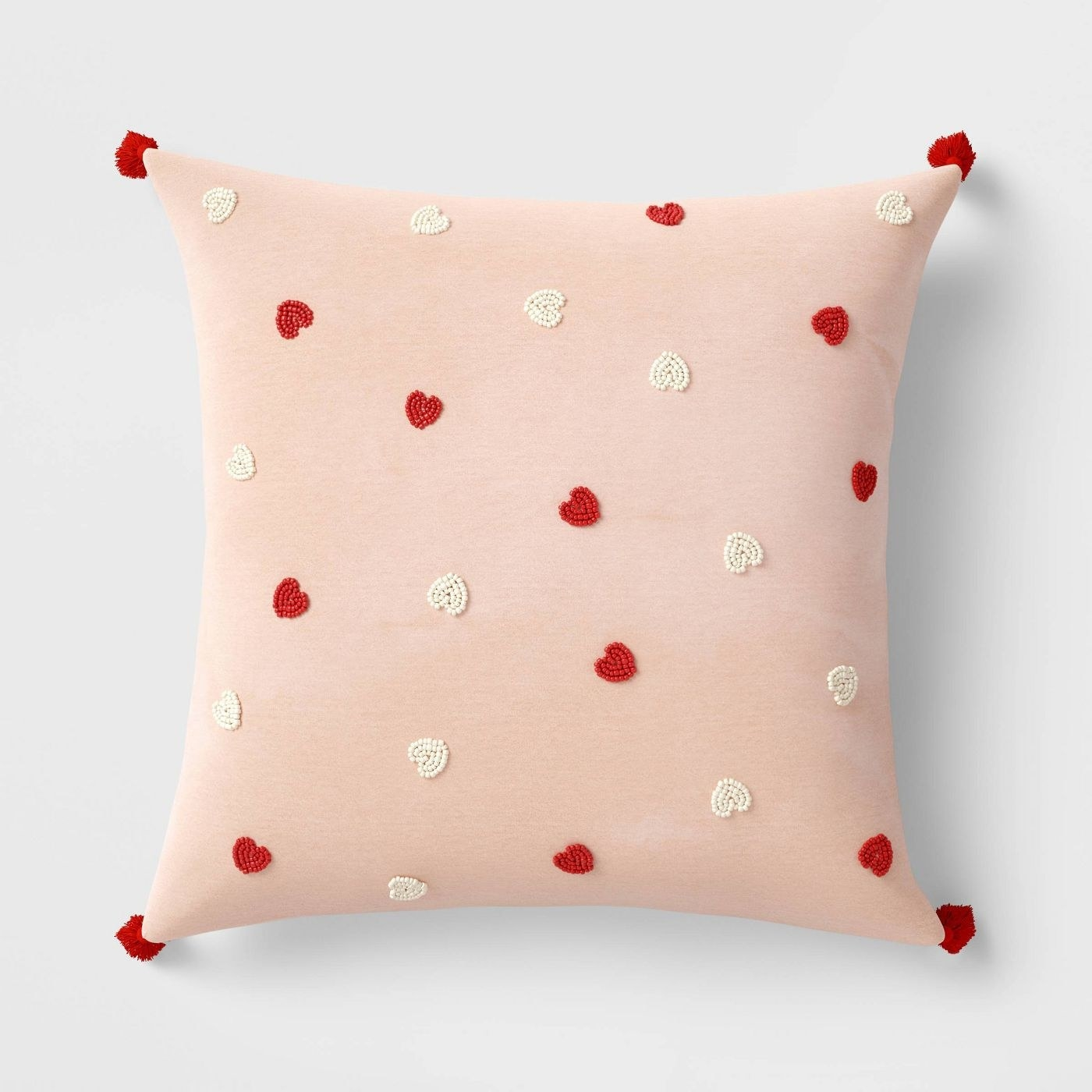 The pillow, which is square, blush-colored, has small red poms at each corner, and is dotted with small beaded hearts in red and white