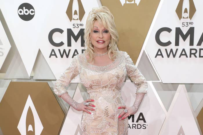 Dolly Parton smiles as she poses with her hand on her hips on the red carpet at the 2019 CMA Awards