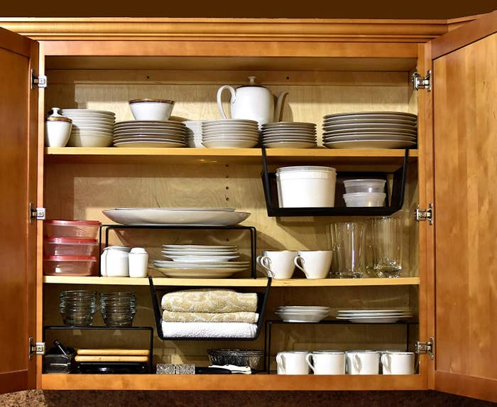 The black metal shelves and baskets in a cabinet