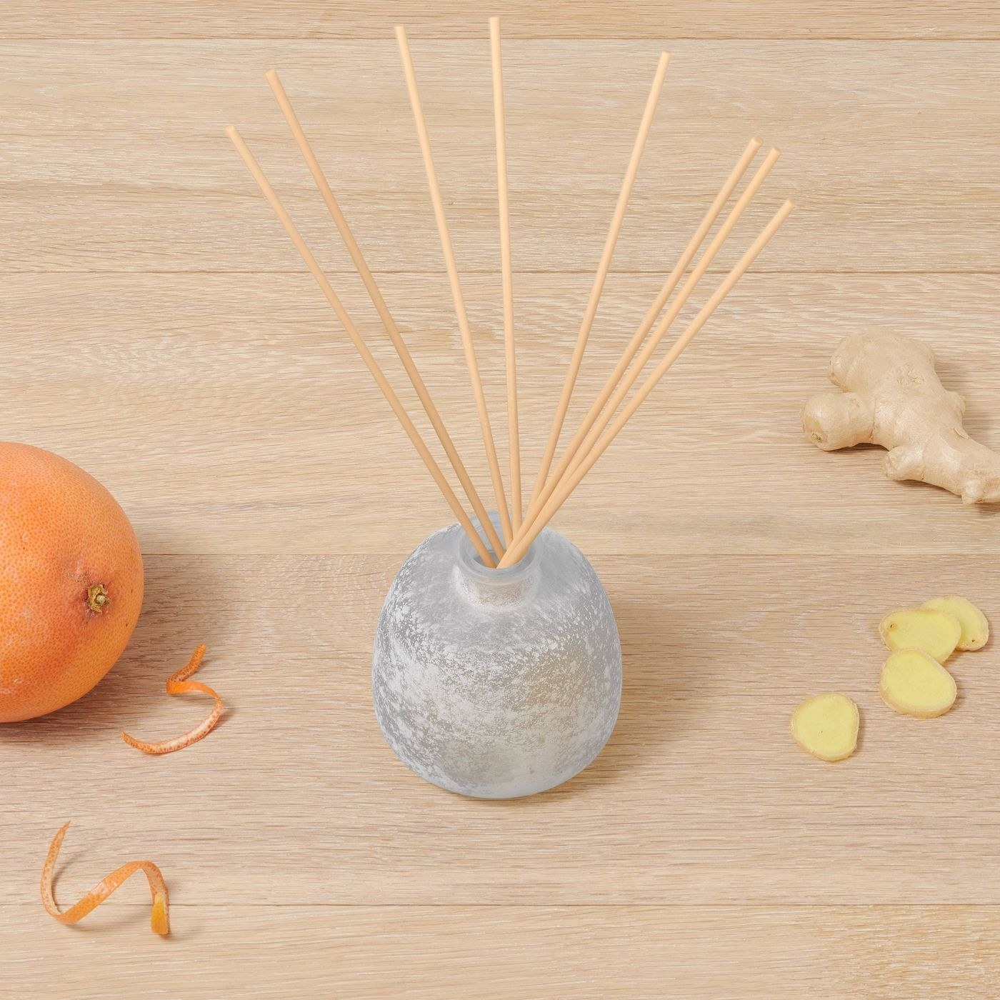 The diffuser, which is gray and shaped like a small round vase