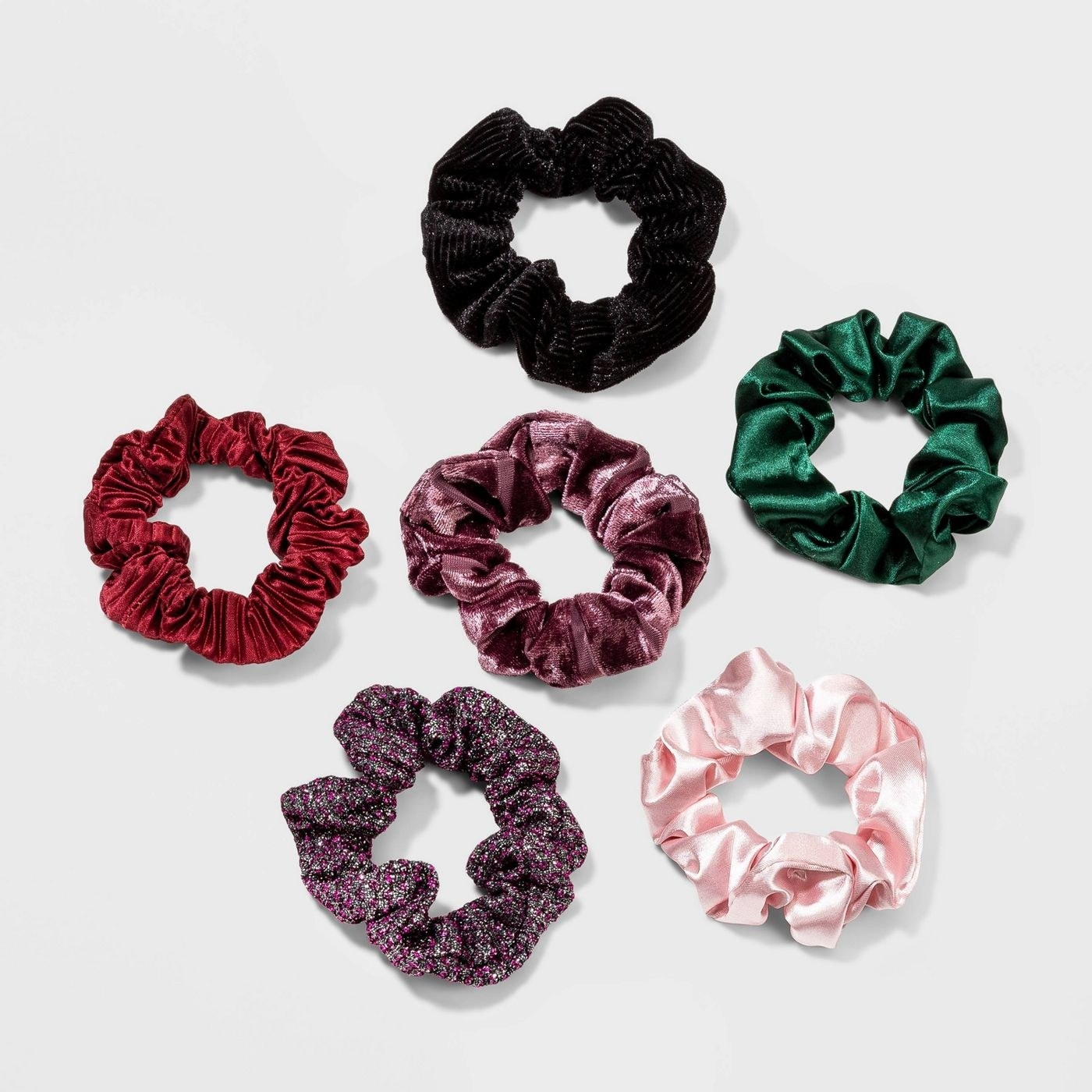Six scrunchies, in a variety of colors and fabric textures, including silky and velvety